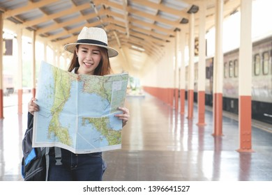 Young Asia woman wanderer with trendy look searching direction on location map while traveling in train station.