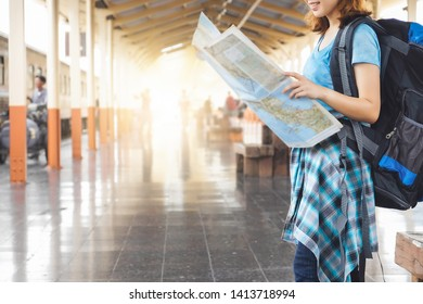 Young Asia woman wanderer with trendy look searching direction on location map while traveling in train station.travel concept.