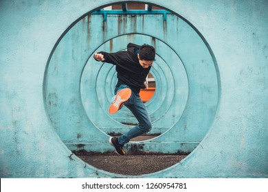 Young Asian active man jumping and kicking action, circle looping wall background. Extreme sport activity, parkour outdoor free running, or healthy lifestyle concept