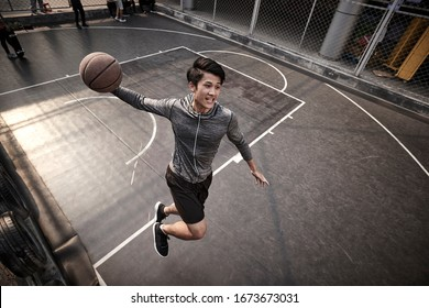 young asian adult male basketball player attempting a slam dunk on outdoor court