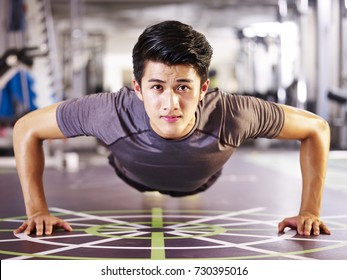 young asian adult man exercising in gym doing pushups, frontal view.
