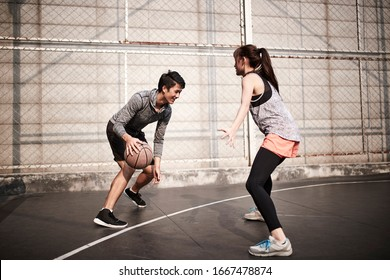 young asian adult man and woman having fun playing basketball on a outdoor court
