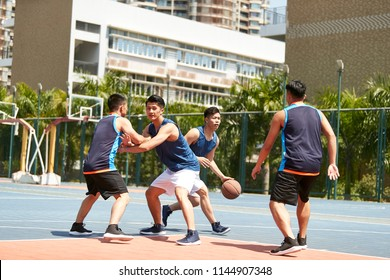 young asian adult players playing basketball on outdoor court.