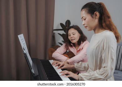 Young asian adult woman learning paino at home, while teacher showing her how to press chord. Placticing, playing music together.