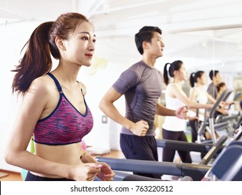 young asian adult working out on treadmill.