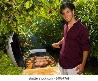 A young Asian American man grilling steaks in his yard.