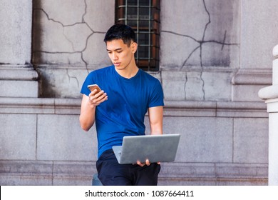 Young Asian American Man studying, working in New York, wearing blue T shirt, black pants, sitting on pillar on old street on campus, working on laptop computer, looking down, texting on cell phone.