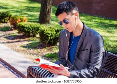 Young Asian American Man traveling, studying in New York, dressing in gray blazer, wearing white earphone, blue sunglasses, listening music, reading red book, sitting on bench in street park.