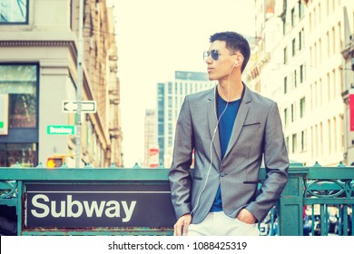 Young Asian American Man traveling in New York, dressing in gray blazer, white pants, wearing sunglasses, earphones, listening music, standing on street by Subway sign, waiting.