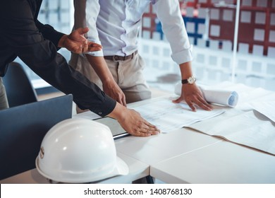 Young asian architect colleagues discussing about construction plans on blueprint and tablet at construction site office. Architect using technology concept.