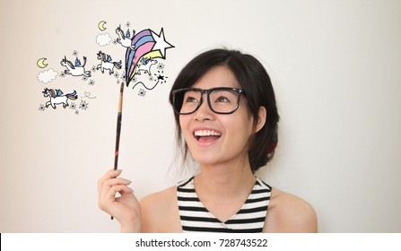 Young asian artist woman wearing glasses  holding pain brush with unicorns and rainbows doodles illustration