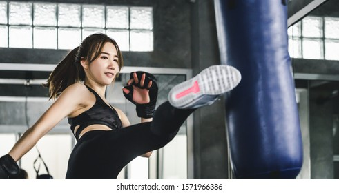 Young asian athlete fitness woman with boxing gloves doing kick boxing training in sport gym