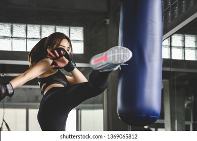 Young asian athlete woman with boxing gloves doing kick boxing training in sport gym