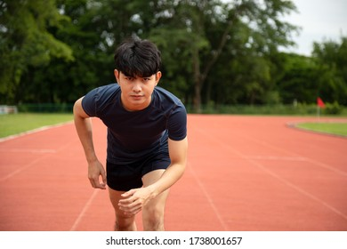 Young Asian Athletic man running in track to practice himself