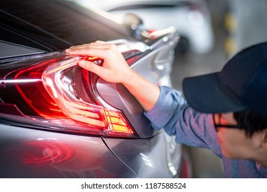 Young Asian auto mechanic checking tail light in auto service garage. Mechanical maintenance engineer working in automotive industry. Automobile servicing and repair concept