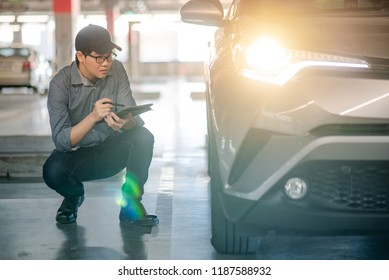 Young Asian auto mechanic holding digital tablet checking headlight in auto service garage. Mechanical maintenance engineer working in automotive industry. Automobile servicing and repair concept