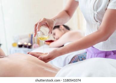 Young asian back oil therapy spa,Masseur pouring aroma oil to hand closeup. Massagist prepare to do oriental spa procedure, having a wellness back massage. Thai massage health care pleasure concept
