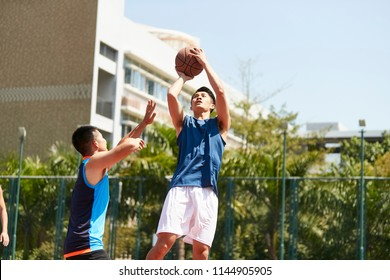 young asian basketball player making a jump shot while opponent playing defense trying to block the ball.