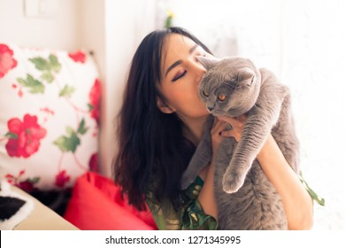 Young Asian beautiful female owner holding and kissing her own adorable British shorthair cat inside room