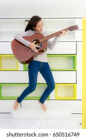 Young Asian beautiful girl hold guitar and jump in her bedroom, using private time as teenager