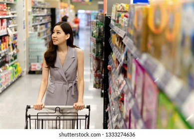 Young Asian beautiful girl pushing shopping cart walking in supermarket. She is looking and choosing things to buy with smile. Seen from her front while she looking on her right. Shopping concept.