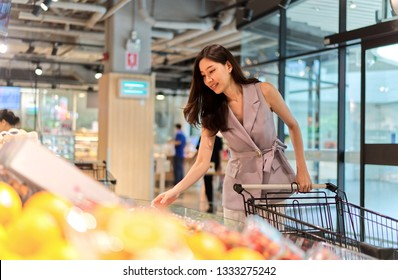 Young Asian beautiful girl pushing cart walking in supermarket. She is looking and picking box of strawberry to put in her shopping cart. She buying daily products for good heath. Healthcare concept.