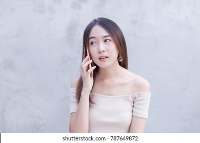 Young Asian beautiful and pretty talkative woman talking the telephone, smartphone or mobile phone