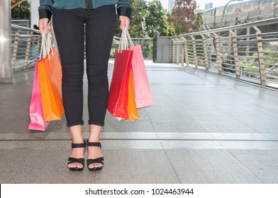 Young Asian beautiful woman big smile holding many color bags from her life style shopping.  Young woman be very happy to shopping a lot of color paper bags in her hands.