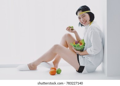 Young Asian beautiful woman eating salad vegetables in diet food concept happy and smiling on white background