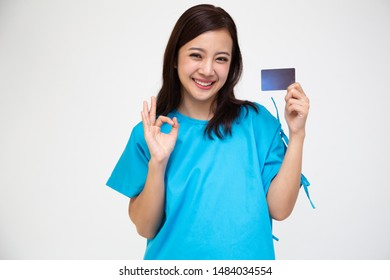 Young Asian beautiful woman patient showing personal accident insurance care card and ok sign isolated on white background, PA and health claim services concept