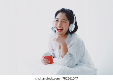 Young Asian beautiful woman relax with music and drink coffee on white background lifestyle concept