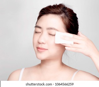 young asian beautiful woman,smiling, holding hands near face,Isolated on a gray Background.Touching her Face. Happy Woman after Bath with Clean Perfect,Use cotton wool to cover the eyes, cheek, lips