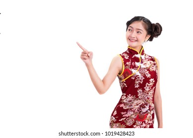 Young Asian beauty woman wearing cheongsam and pointing beside gesture in Chinese new year festival event on isolated white background. Holiday and Lifestyle concept. Qipao dress wearing