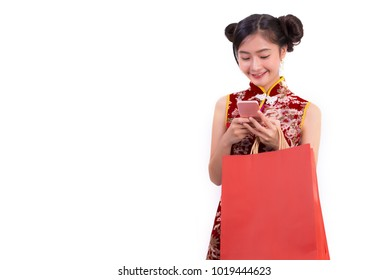 Young Asian beauty woman wearing cheongsam and using smart phone gesture in Chinese new year festival event on isolated white background. Technology and Holiday lifestyle concept. Qipao dress wearing