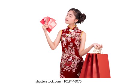 Young Asian beauty woman wearing cheongsam and holding moneys as millionaire gesture in Chinese new year festival event on isolated white background. Holiday and Lifestyle concept. Qipao dress wearing
