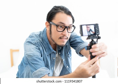 Young Asian blogger setting camera video with recording filming at home.making vlog. vlog concept