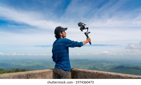 Young asian blogger or vlogger looking at camera and talking on video shooting with technology. Social media influencer people or content creator.