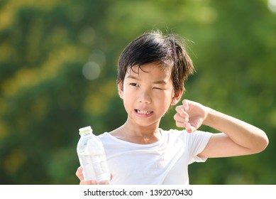 Young Asian boy carry a bottle of water and feel hot in a summer day in a park