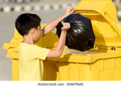Young Asian boy carry garbage in plastic bag for eliminate in the yellow bin under the sunlight