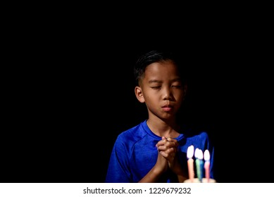 Young Asian boy celebrate and blow the candle of his birthday cake in a dark room.