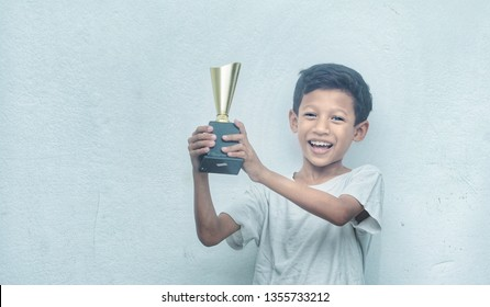 Young Asian boy celebrating his winning trophy. Toned image