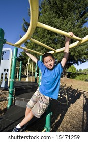 Young Asian boy climbing on jungle gym. He is smiling at camera. Vertically framed photo.
