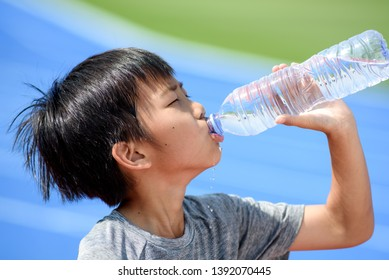 Young Asian boy drink water from a plastic bottle under the sunlight beside a running track to reduce his thirsty.