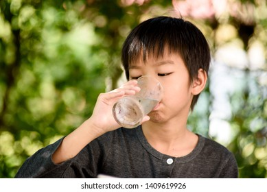 Young Asian boy drink a water from glass in a garden after meal