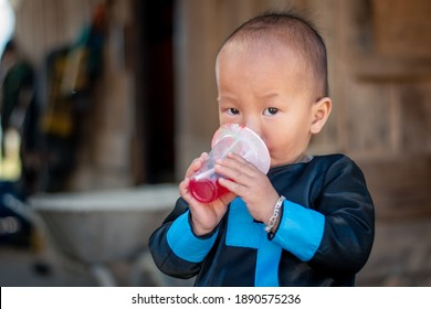 Junge asiatische Junge trinkt süß, glücklich mit seinem Getränk, Porträt mit Textkopie, Kleidung aus ethnischen Gruppen