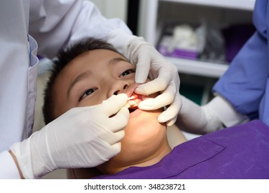 Young asian boy during dental extraction.