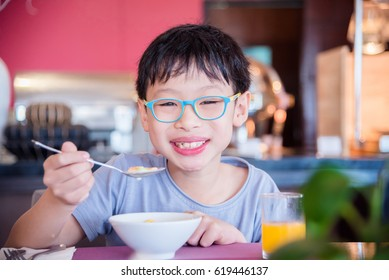 Young asian boy eating cereal for breakfast
