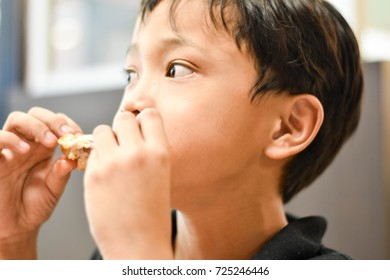The young Asian boy is eating the fried chicken wing looks yummy in the restaurant.