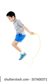 Young asian boy exercise with yellow rubber rope jumping on white background