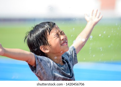 Young Asian boy fell freshness after get the water drop under the sunlight next to a running track.